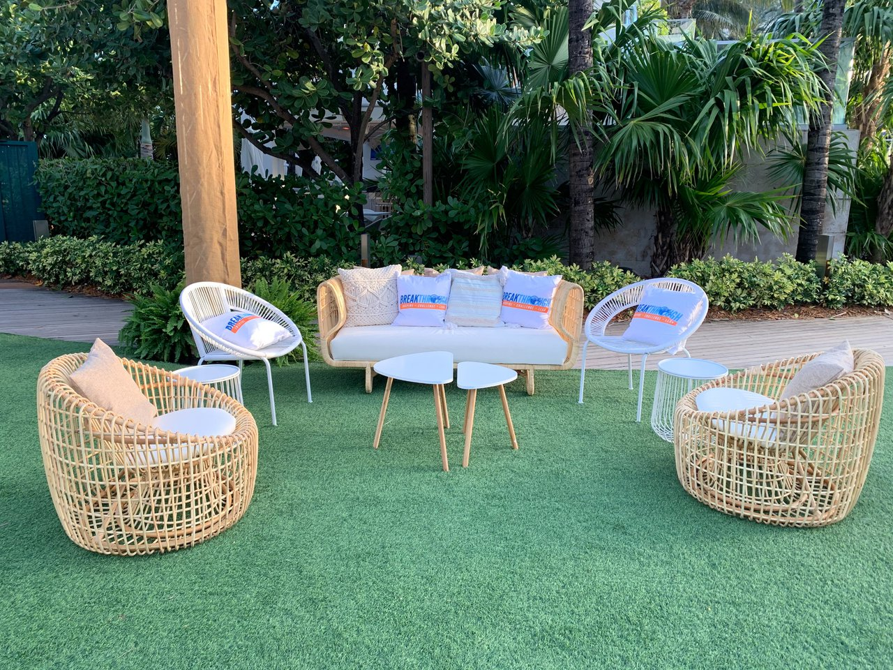 Seaside Soiree photo Boho rattan furniture grouping with custom branded pillows and white wire chairs.jpg